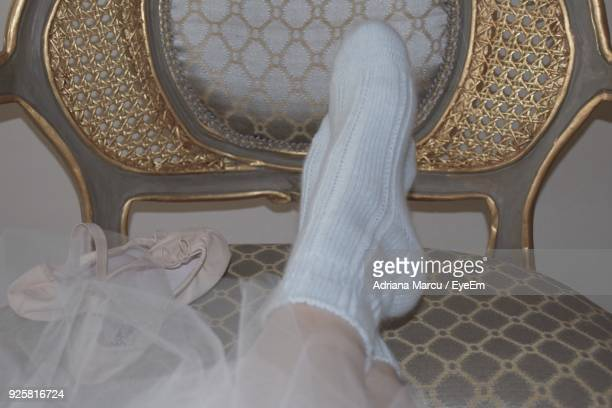 Low Section Of Woman Sitting On Chair