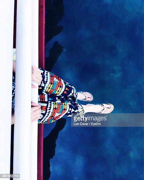 low section of woman sitting on jetty over lake - jetty stock pictures, royalty-free photos & images