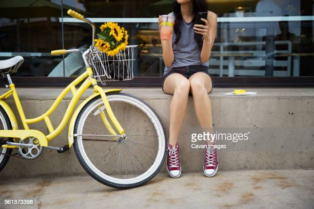 Low section of woman sitting on retaining wall by bicycle