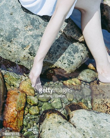 Low Section Of Woman Sitting On Rocks At Beach During Sunny Day