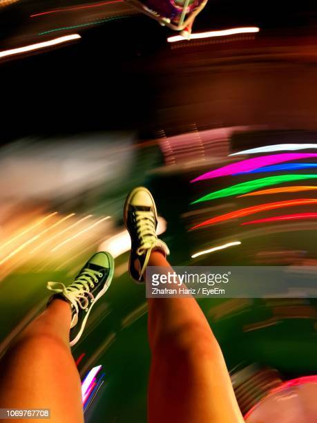 low section of woman sitting on spinning amusement park ride at night - amusement park ride stock pictures, royalty-free photos & images