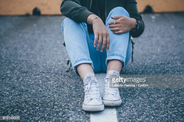Low Section Of Woman Sitting On Street