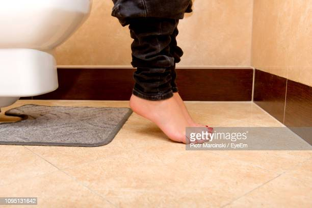 low section of woman sitting on toilet bowl in bathroom - femme wc photos et images de collection