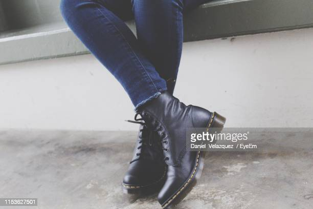 low section of woman sitting on wall - black boot stock pictures, royalty-free photos & images
