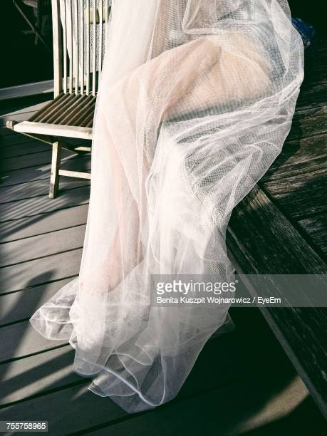 low section of woman sitting on wooden bench with white tulle netting - チュール生地 ストックフォトと画像