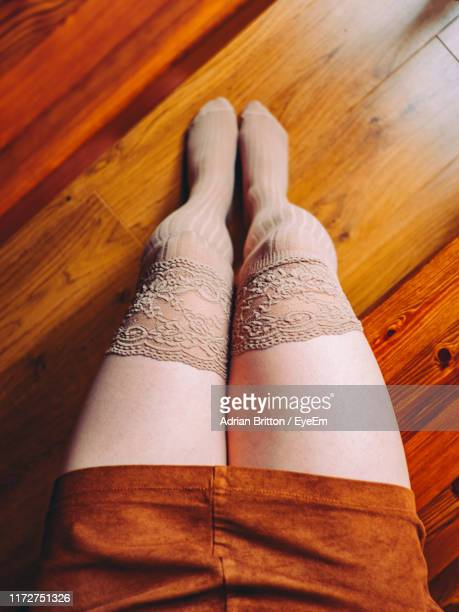 low section of woman sitting on wooden floor - legs and short skirt sitting down stock pictures, royalty-free photos & images