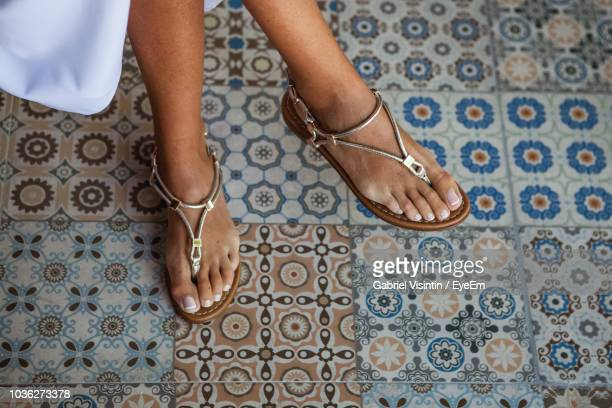 low section of woman sitting over tiled floor - sandal stock pictures, royalty-free photos & images
