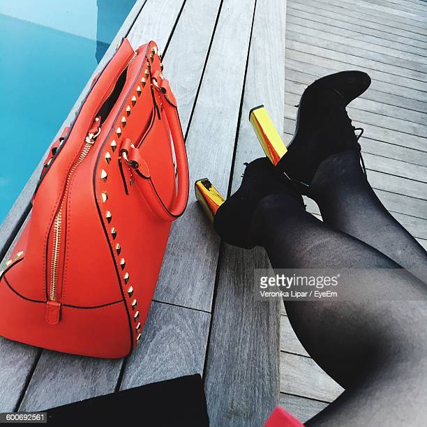 low section of woman sitting with orange purse on boardwalk - gold shoe stock photos and pictures