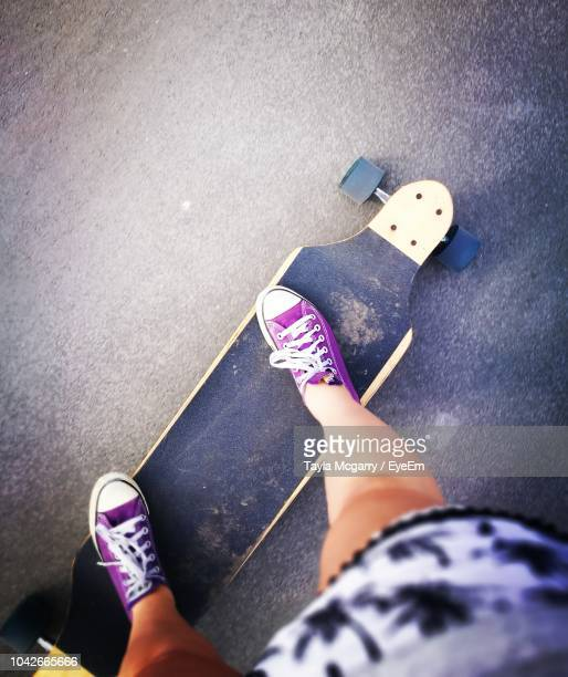 low section of woman skateboarding on road - purple shoe stock pictures, royalty-free photos & images