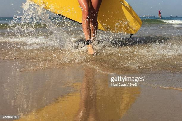 Low Section Of Woman Splashing Water In Sea