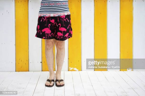 low section of woman standing against striped wall - ショートパンツ ストックフォトと画像