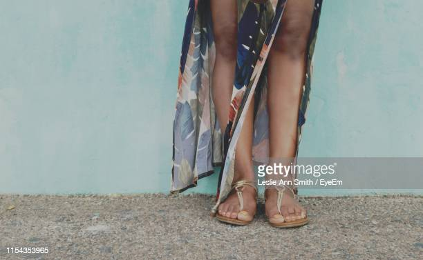 low section of woman standing against wall - sandal stock pictures, royalty-free photos & images