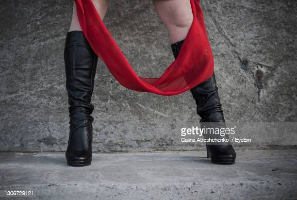 low section of woman standing against wall - black shoe stock pictures, royalty-free photos & images