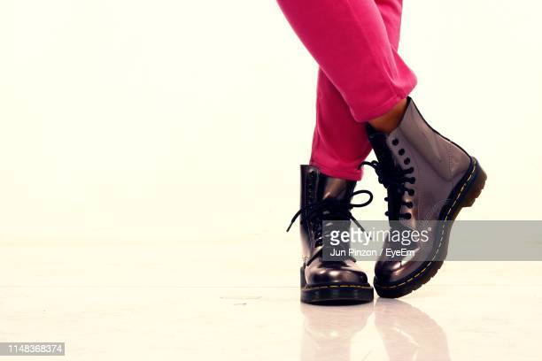 low section of woman standing against white background - leather boot stock pictures, royalty-free photos & images