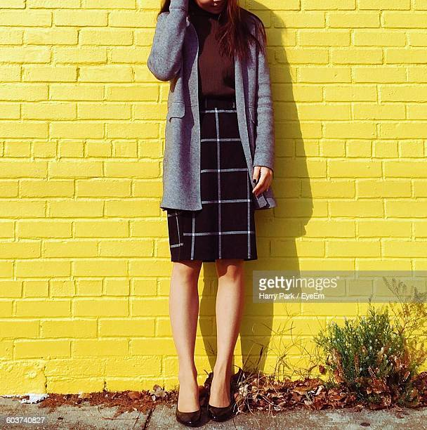 Low Section Of Woman Standing Against Yellow Brick Wall