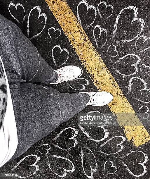Low Section Of Woman Standing Amidst Heart Shape Drawn On Footpath