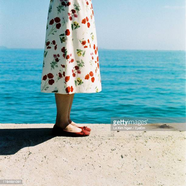 low section of woman standing at beach - robe à motif floral photos et images de collection
