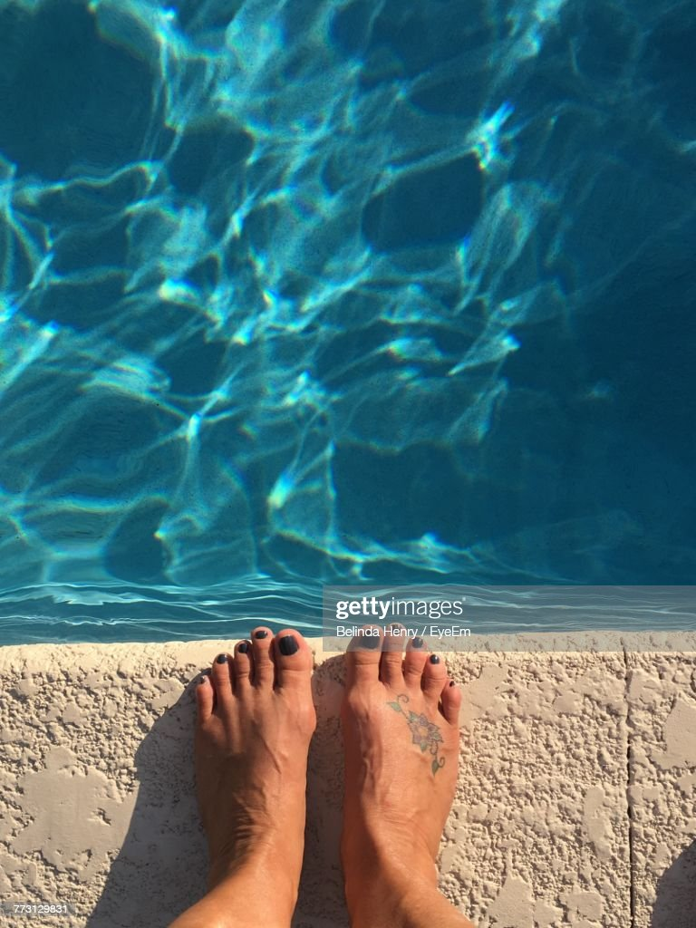 Low Section Of Woman Standing At Poolside : Photo