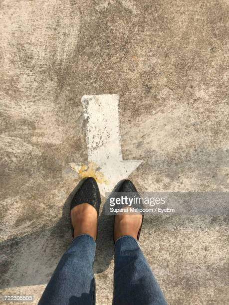 Low Section Of Woman Standing By Arrow Sign On Road