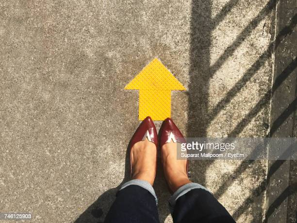 Low Section Of Woman Standing By Arrow Symbol On Street