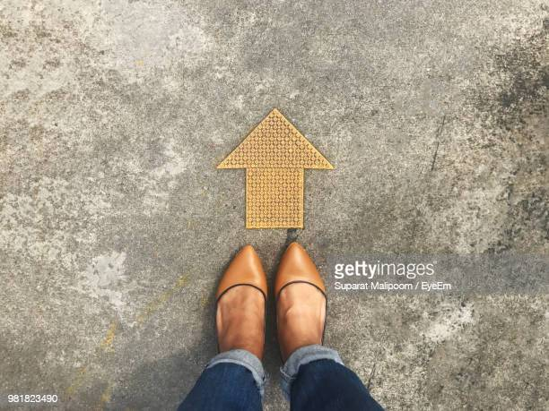 low section of woman standing by arrow symbol - arrow stock photos and pictures