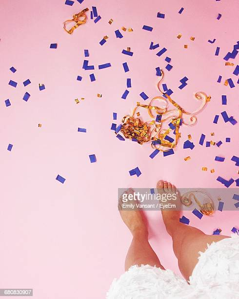 Low Section Of Woman Standing By Confetti On Floor
