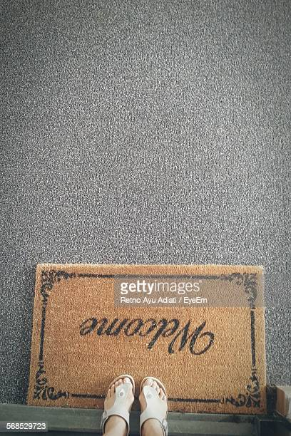 Low Section Of Woman Standing By Door Mat