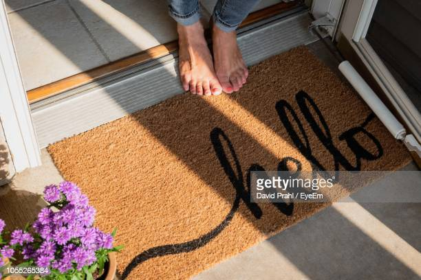 low section of woman standing by doormat with hello text - greeting stock pictures, royalty-free photos & images