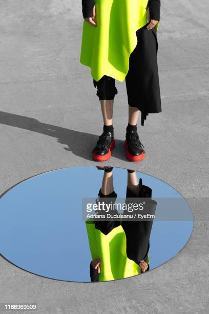 low section of woman standing by mirror on footpath - ペア ストックフォトと画像