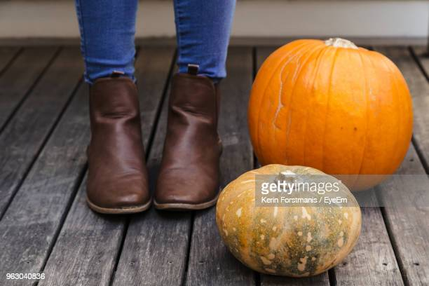Low Section Of Woman Standing By Pumpkins On Hardwood Floor