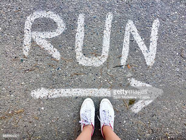 Low Section Of Woman Standing By Run Text With Arrow Symbol On Road