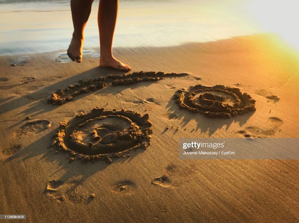Low Section Of Woman Standing By Smiley Face On Shore At Beach : Stock Photo