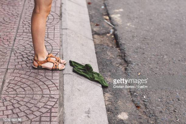 low section of woman standing by socks on footpath - bortes imagens e fotografias de stock