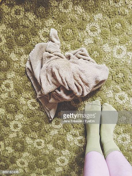 Low Section Of Woman Standing By Towel On Carpet
