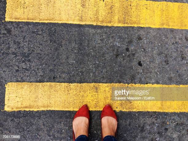 low section of woman standing by yellow markings on road - yellow shoe stock pictures, royalty-free photos & images