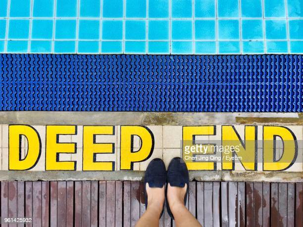 low section of woman standing by yellow text on poolside - human leg stock photos and pictures