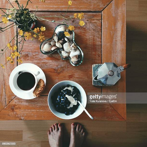 Low Section Of Woman Standing Food And Black Coffee On Table