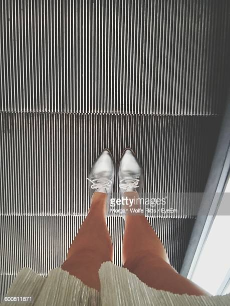 low section of woman standing in escalator - silver shoe stock pictures, royalty-free photos & images