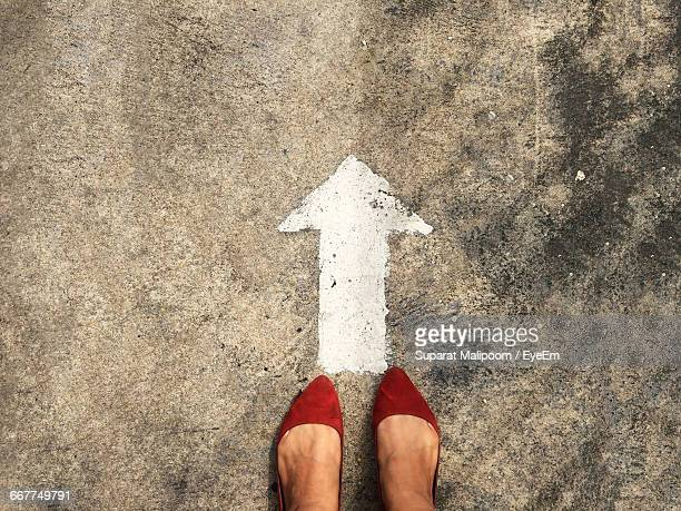Low Section Of Woman Standing In Front Of Arrow Sign On Road
