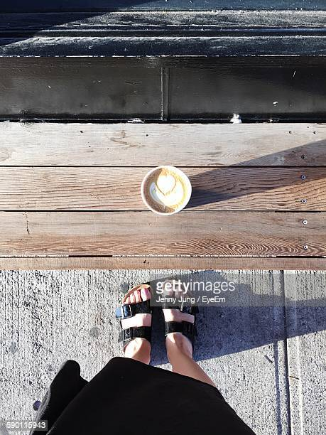 Low Section Of Woman Standing In Front Of Coffee On Bench