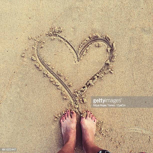Low Section Of Woman Standing In Front Of Heart Shape On Sandy Beach