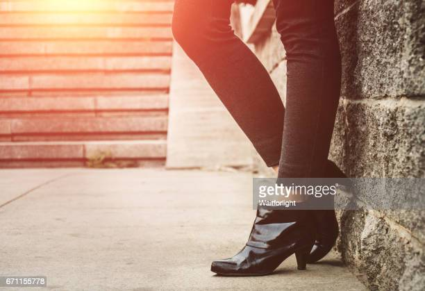 low section of woman standing leaning against the wall - ブーツ ストックフォトと画像
