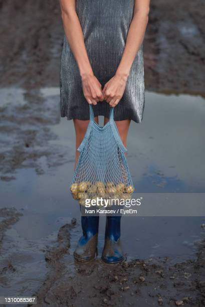 low section of woman standing on beach - silver boot stock pictures, royalty-free photos & images