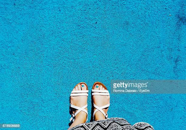 low section of woman standing on blue concrete footpath - blue shoe stock pictures, royalty-free photos & images