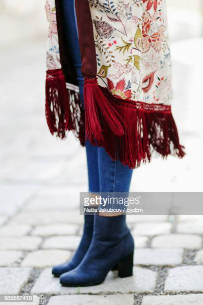 low section of woman standing on cobbled footpath - human leg stock photos and pictures