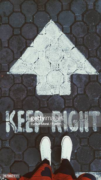 Low Section Of Woman Standing On Cobblestone Street By Arrow Symbol