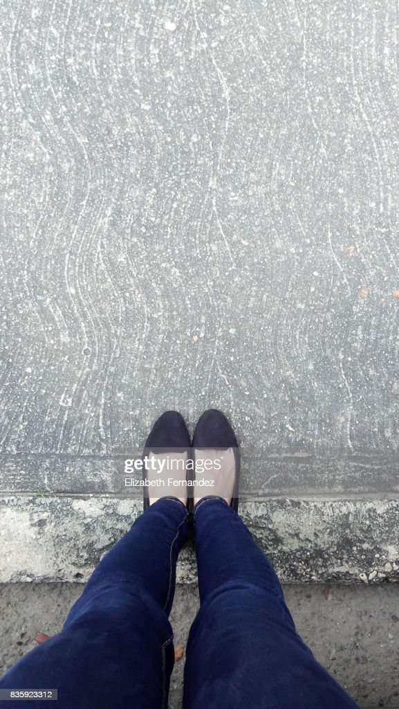 Low Section Of Woman Standing On Concrete : Stock Photo