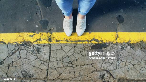 Low Section Of Woman Standing On Cracked Footpath
