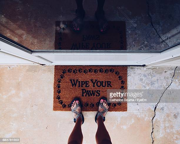 Low Section Of Woman Standing On Doormat