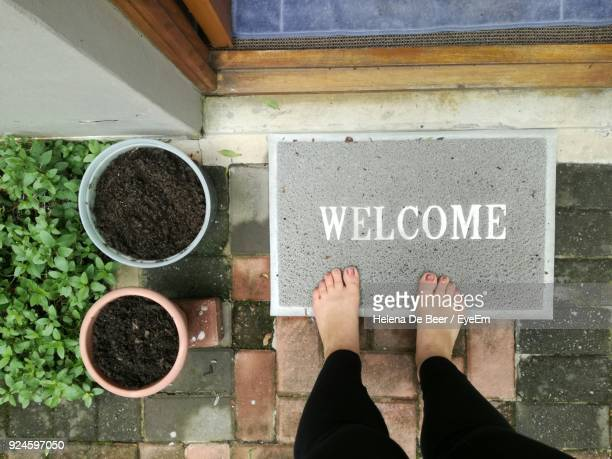 Low Section Of Woman Standing On Doormat With Welcome Sign